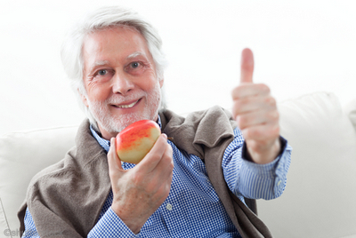 Man eating an apple while giving a thumbs up