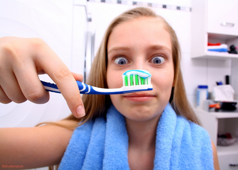 girl holding a tooth brush looking at it cross-eyed