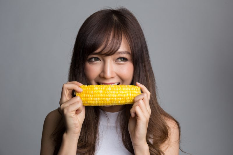 Woman biting into a corn cob without hurting her teeth