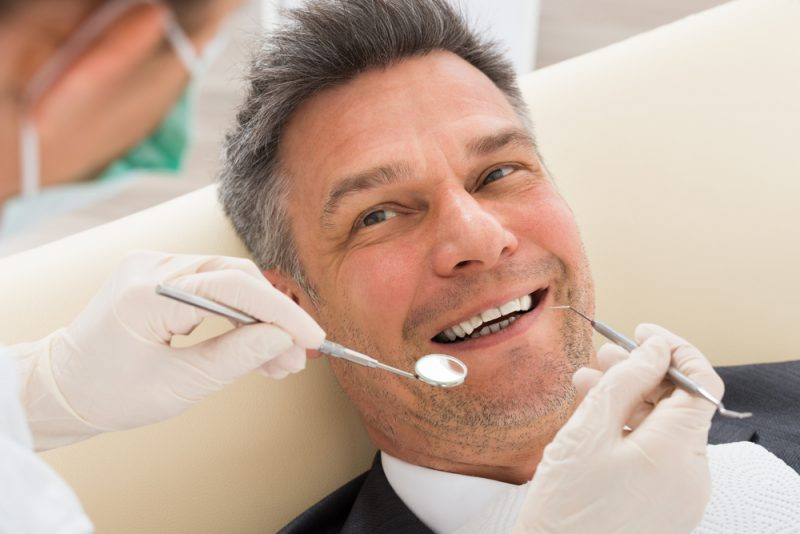 Man smiling while getting a dental exam