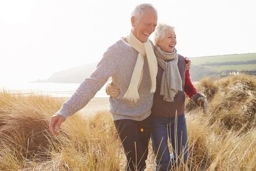 Elderly couple smiling while walking outside