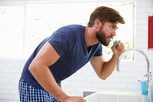 Man brushing his teeth to prevent cavities