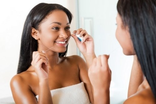 Woman flossing in front of a mirror