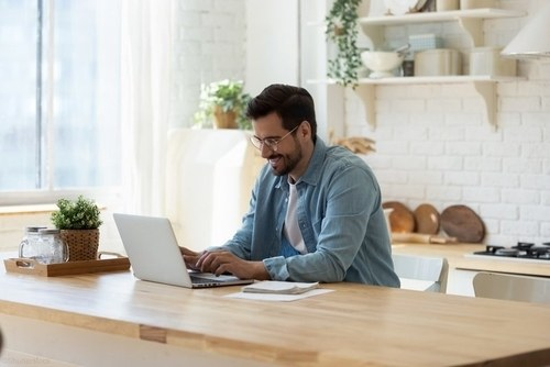 man at home on computer smiling while working