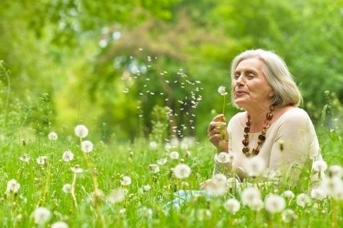happy elder woman in dandelion field blowing out seeds