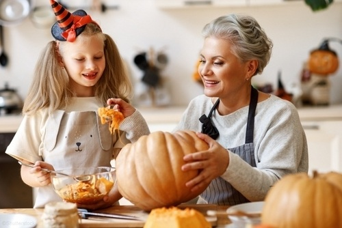 young girl and grandmother carving pumpkins in the kitchen