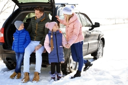 family bundled up out in the snow weather